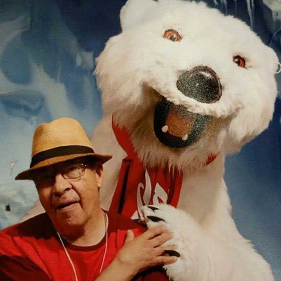 Man in a hat takes a moment to take a picture with the Coca-Cola bear.