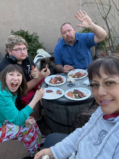 Family of four enjoying a wonderful dinner outside. They are super excited!