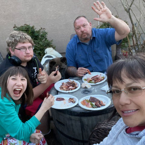 Family of four enjoying a wondering meal outdoors. They look super excited about their photo-op.
